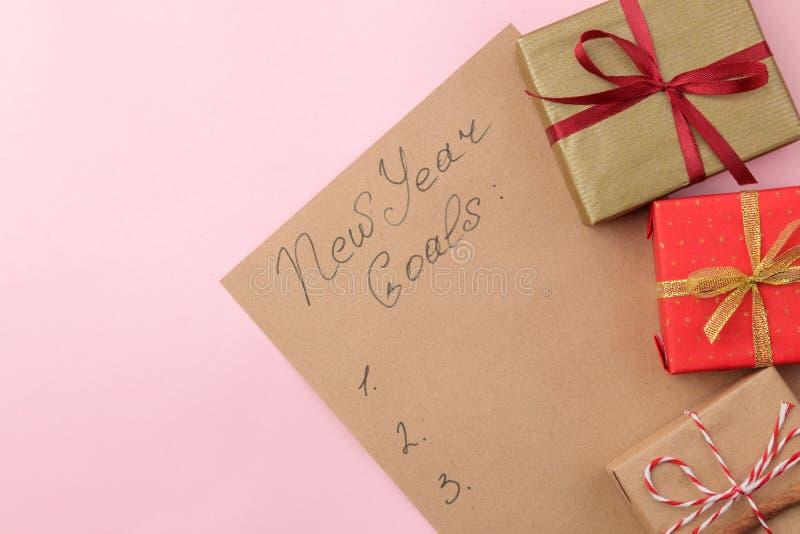 Nouvelles années de buts 2019 Texte sur un morceau de papier avec les cadeaux de nouvelle année sur un fond rose lumineux images libres de droits