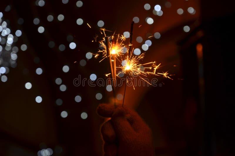 Nouvelles années de célébration de la veille avec les feux d'artifice tenus dans la main de cierge magique images libres de droits