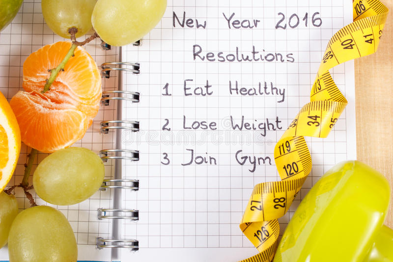 Nouvelles années de résolutions écrites en carnet et fruits, haltères de centimètre images stock