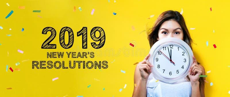2019 nouvelles années de résolutions avec la jeune femme tenant une horloge photographie stock