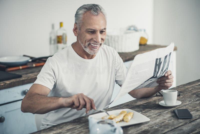 Nouvelles contestées de lecture d'homme pendant le petit déjeuner images stock