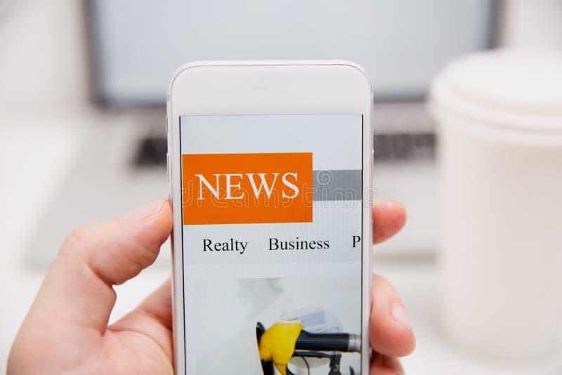 Nouvelles en ligne dans le téléphone portable Fermez-vous de l'écran de smartphone Articles de lecture d'homme dans l'application photos stock