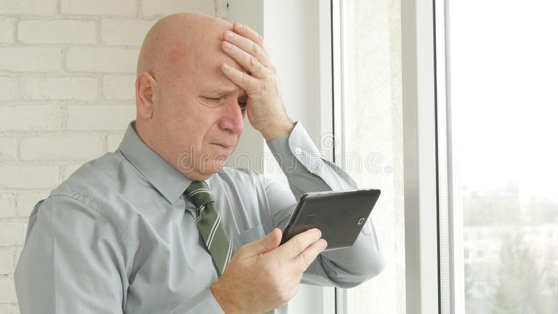 Nouvelles financières d'Image Reading Upset d'homme d'affaires sur la Tablette et le renversement de faire des gestes photographie stock libre de droits