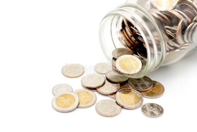 Nouvelles pièces de monnaie de baht thaïlandais débordant un pot en verre photographie stock