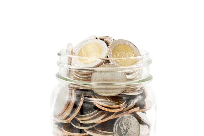 Nouvelles pièces de monnaie de baht thaïlandais dans un pot en verre photos stock