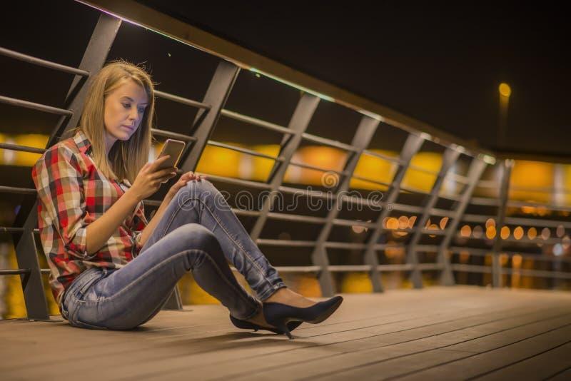 Nouvelles tristes La jeune femme bouleversée avec le téléphone portable lit le message images libres de droits