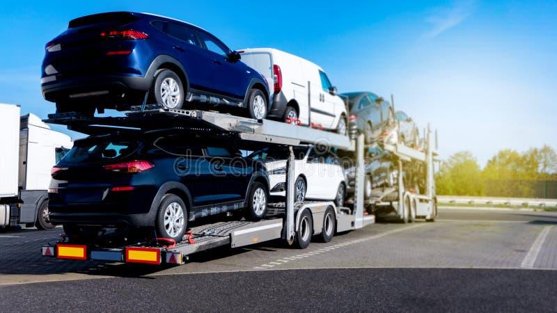 Nouvelles voitures sur le camion Nouvelles voitures de transport photographie stock