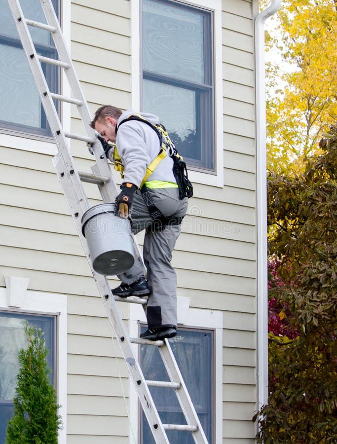 Man on ladder cleaning gutters royalty free stock photography