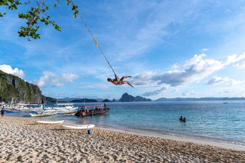 A woman on a swing at the 7 commandos island beach in a El nido, Palawan, Philippines, Nov 18,2018 A. Nov 18,2018 A woman on a swing at the 7 commandos island stock photography