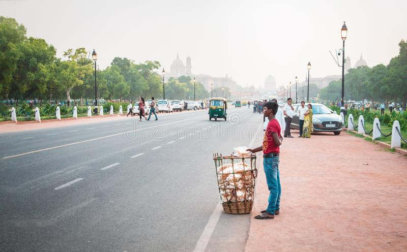 Nova Deli, ?ndia - 1? de junho de 2019: Uma jovem crian?a que vende petiscos perto de Rashtrapati Bhawan nas ruas fotos de stock
