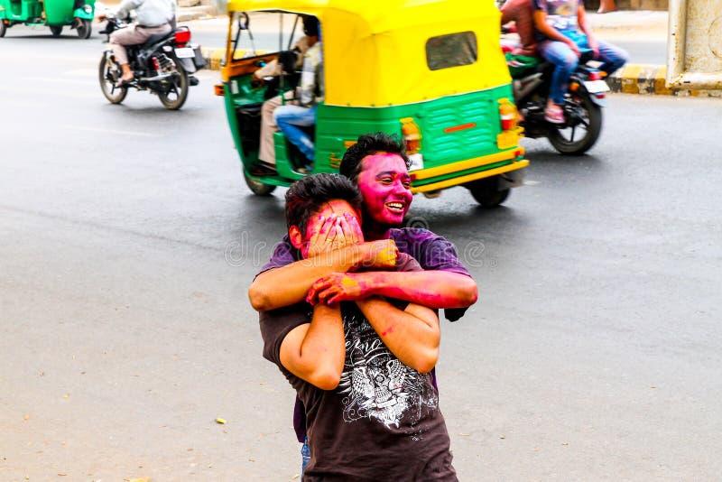 Nova Deli, Índia - 10 de março de 2016: os meninos indianos novos com caras coloridas comemoram o festival do holi nas ruas e têm imagem de stock