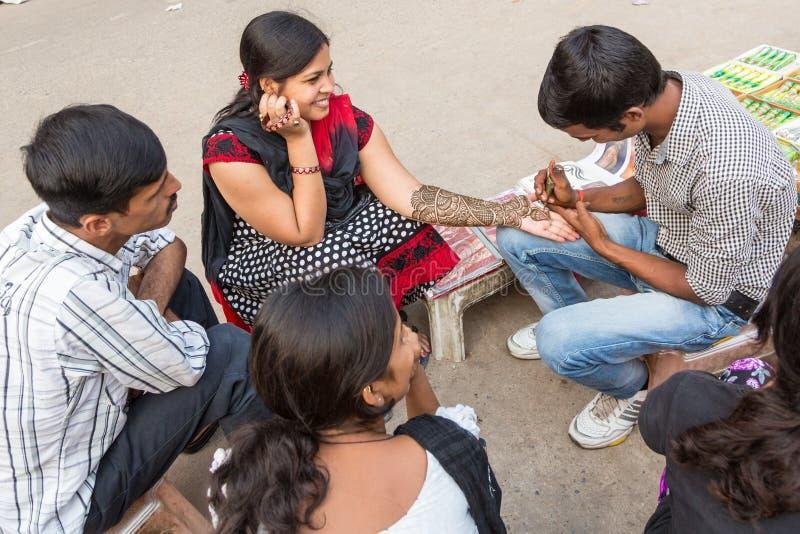 Nova Deli, Índia - 6 de outubro de 2013: Um homem faz um tatoo da hena sobre fotos de stock royalty free