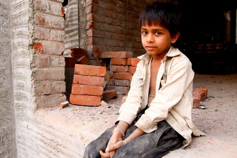 Nova Deli, Índia - 20 de outubro de 2017: retrato do menino indiano novo que trabalha como o pedreiro na construção com roupa suj fotos de stock