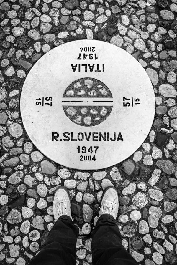 Nova Gorica Slovenia - Gorizia Itália: Equipe os pés do ` s nas calças de brim e nas sapatilhas que estão na beira entre Eslovêni imagens de stock