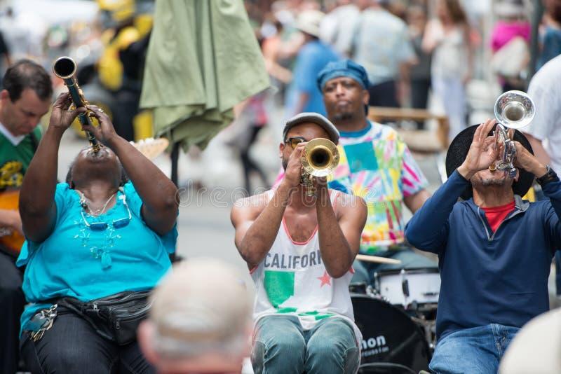 NOVA ORLEÃES - 13 DE ABRIL: Em Nova Orleães, uma banda de jazz joga melodias do jazz na rua para doações dos turistas fotos de stock royalty free