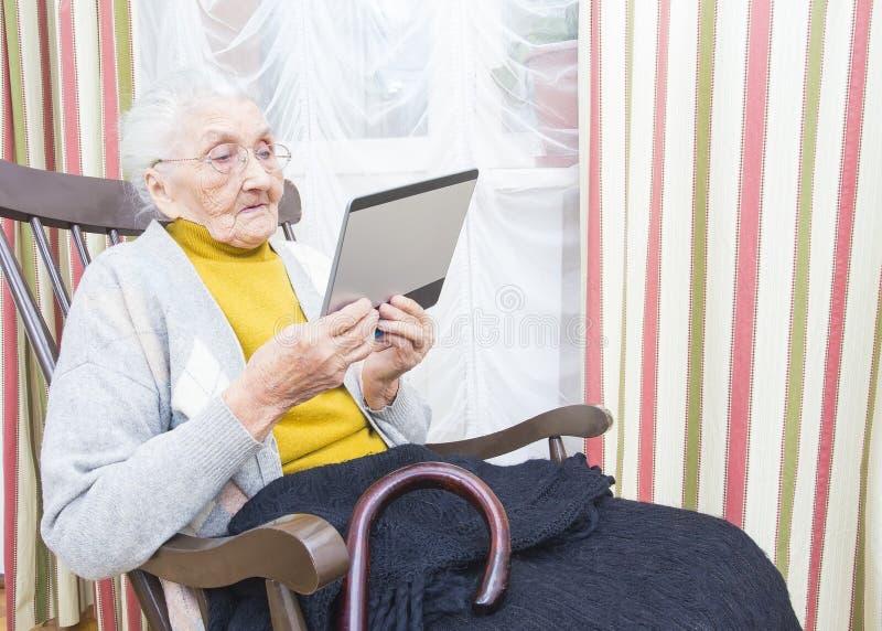 Nova tecnologia idosa da senhora imagens de stock