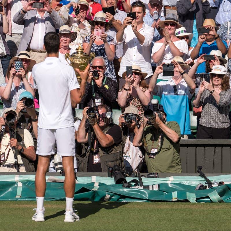 Novac Djokovic, giocatore serbo, vince Wimbledon Nella foto tiene il trofeo sulla corte del centro davanti ai fotografi di stampa immagine stock