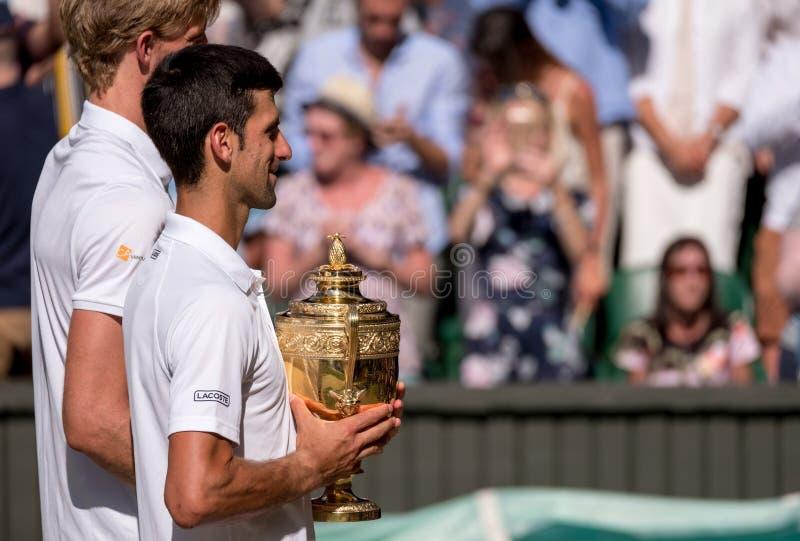 Novac Djokovic, vincitore di Wimbledon, tiene il trofeo sulla corte del centro con Kevin Anderson che sta al suo lato, oscurato p immagine stock