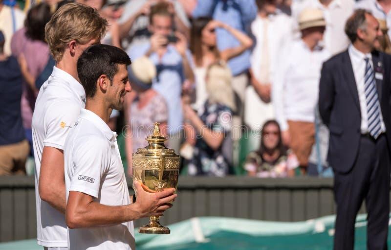 Novac Djokovic, vincitore di Wimbledon, tiene il trofeo sulla corte del centro con Kevin Anderson che sta al suo lato, oscurato p fotografia stock libera da diritti