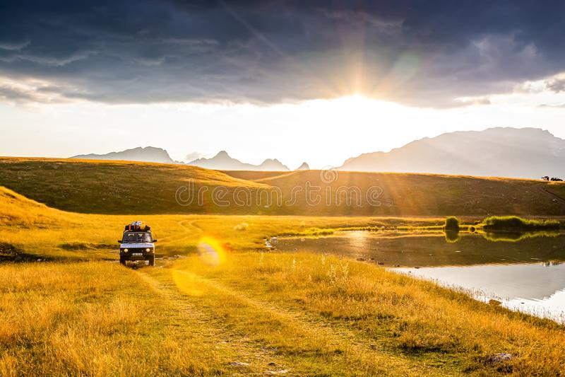 Novakovici, Montenegro - July 20, 2019. Old vintage off road car by paradise Vrazje lake in sunset, Durmitor, Montenegro, Europe royalty free stock photos