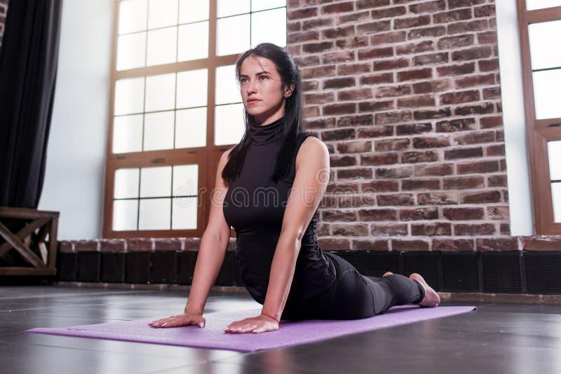 Novato fêmea da ioga que faz a pose da cobra do bhujangasana na esteira no apartamento do sótão fotografia de stock royalty free
