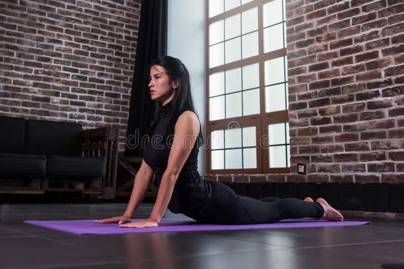 Novato fêmea da ioga que faz a pose da cobra do bhujangasana na esteira no apartamento do sótão fotos de stock royalty free