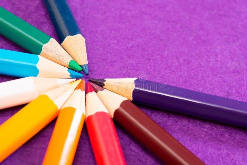 Nove lápis coloridos em um fundo roxo de feltro Lápis coloridos diferentes com espaço para o texto De volta à escola imagens de stock