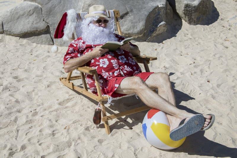 Novela de la lectura de Santa Claus en la playa soleada imágenes de archivo libres de regalías
