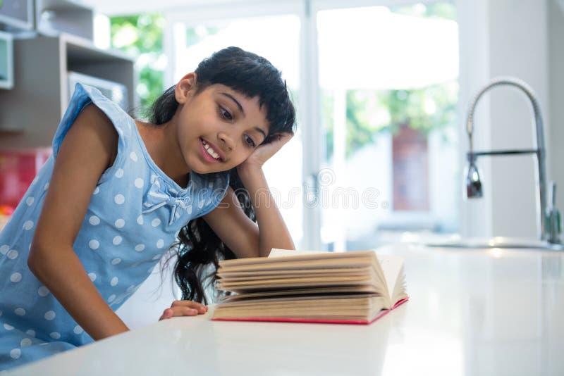 novela de sorriso da leitura da menina no contador de cozinha fotografia de stock