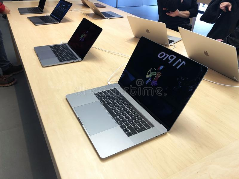 November 2019 Bologna, Italy: Macbooks computers on display in Apple store close-up across shoppers. Apple computers screens on tables royalty free stock photography