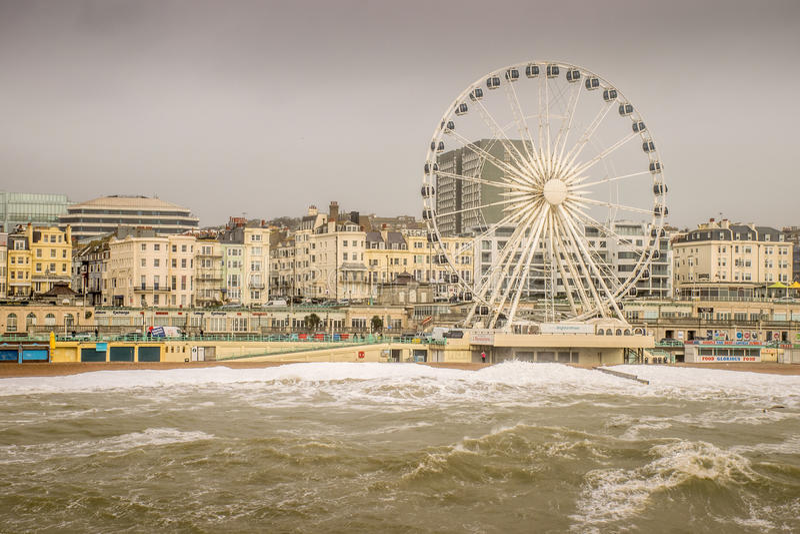 Dangerous waves threaten promenade and big wheel. stock photography