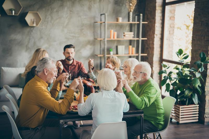 November fall holiday family gathering sit table with thanksgiving lunch dishes hold hand pray prayers senior preteen royalty free stock image