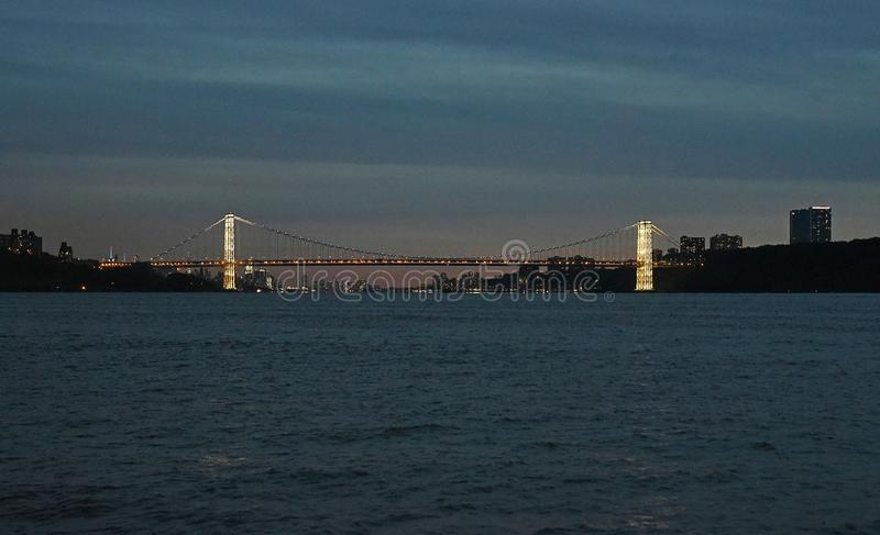 November 11, 2017, The Hudson River, Near Inwood Park, New York City. The Brightly Lit Towers of The George Washington Bridge Can. Be Seen At Dusk. This is shot stock image