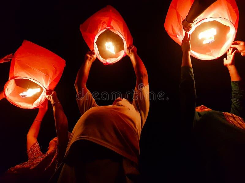 November 2018, Kolkata, Indien Person som tre släpper den tända pappers- ballongen för varm luft i himmellyktafestival på natten  arkivfoto