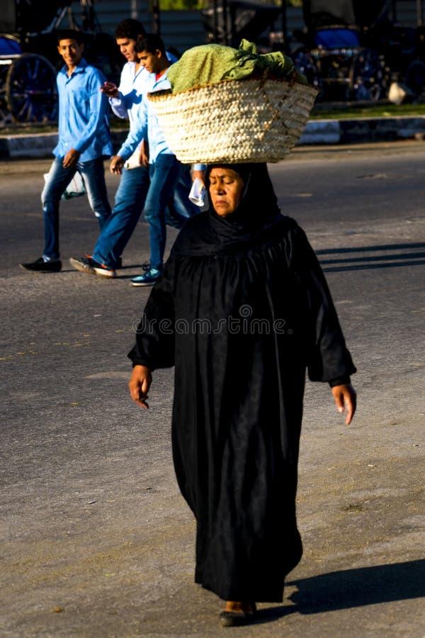 November 2019, LUXOR, EGYPT - Moslem vrouw met mand op haar hoofd Egypte gaat winkelen in Luxor Souq stock foto