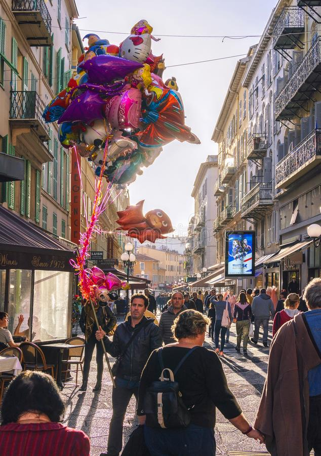 Man Selling Colourful Balloons in Nice. 2 November 2018 - Nice, France. A man walking with colourful balloons in the old town of Nice, France royalty free stock photography