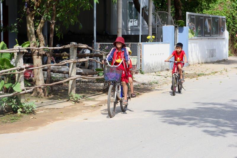 November 2018, School children boy girls uniform cycling village street, Vietnam. School children, boy and girls, in red uniforms are cycling from school back stock photo