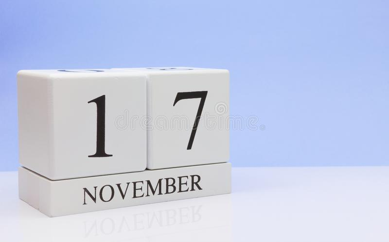 November 17st. Day 17 of month, daily calendar on white table with reflection, with light blue background. Autumn time, empty. Space for text stock images