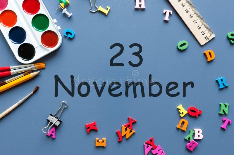 23. November Tag 23 des letzten Herbstmonats, Kalender auf blauem Hintergrund mit Schulbedarf Frau und Männer, die Kenntnisse neh lizenzfreie stockfotografie