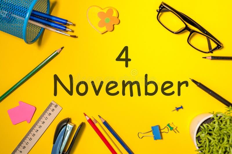 4. November Tag 4 des letzten Herbstmonats, Kalender auf gelbem Hintergrund mit Büroartikel Frau und Männer, die Kenntnisse nehme stockfotografie