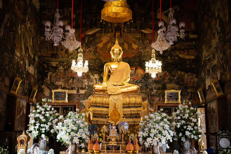 November 20th, 2018 - Bangkok THAILAND - Big golden Buddha surrounded by white orchids in thai temple stock image