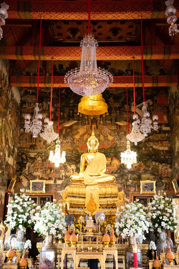 November 20th, 2018 - Bangkok THAILAND - Big golden Buddha surrounded by white orchids in thai temple royalty free stock photography