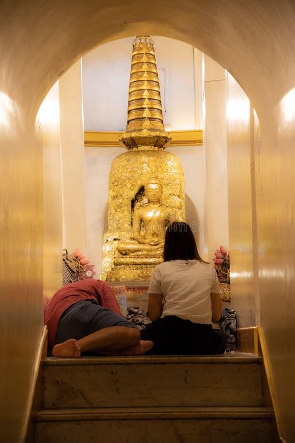 November 20th, 2018 - Bangkok THAILAND - par som ber till den guld- Buddha i thai tempel arkivfoto