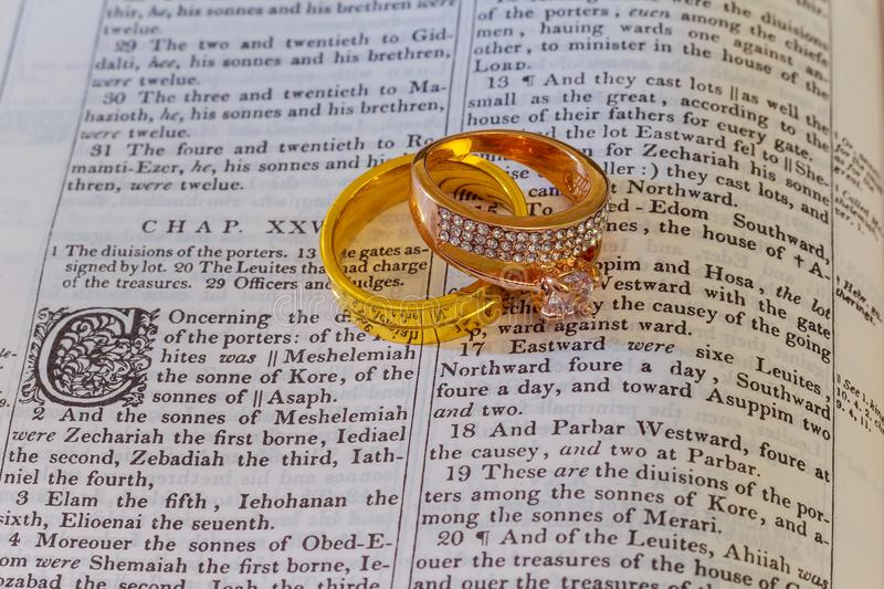 november 04 2016 Wedding rings place on an open Bible to a verse in the book of Genesis marriage. royalty free stock photography