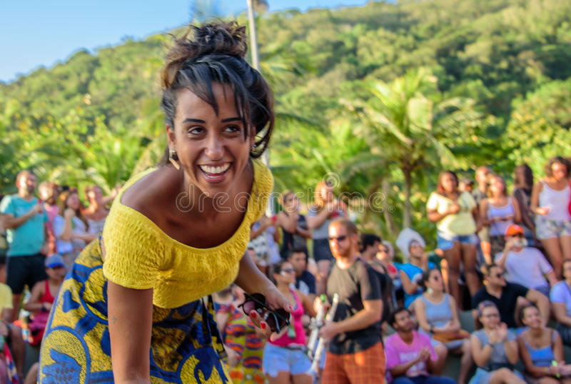 27 November, 2016. Woman in yellow blouse laughing and dancing in the street at sunny day at Leme district, Rio de Janeiro, Brazil stock photography