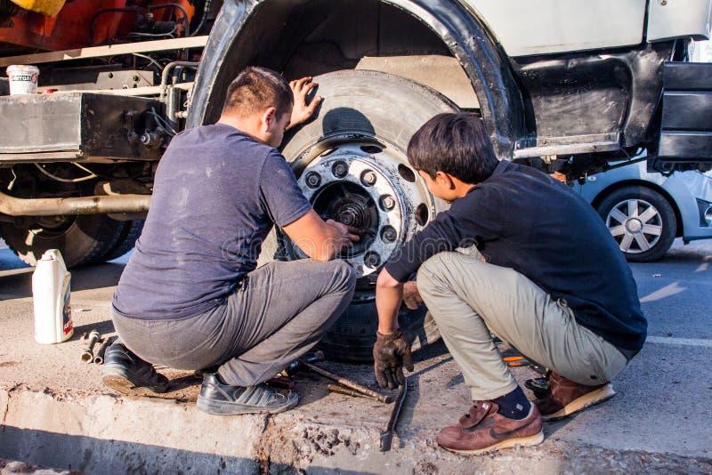 12 novembre 2019,Tashkent, Uzbekistan fila di negozi con verdure sul marciapiede due uomini che riparano una ruota del camion immagini stock