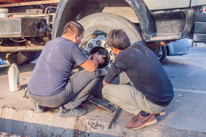 12 novembre 2019,Tashkent, Uzbekistan fila di negozi con verdure sul marciapiede due uomini che riparano una ruota del camion fotografia stock