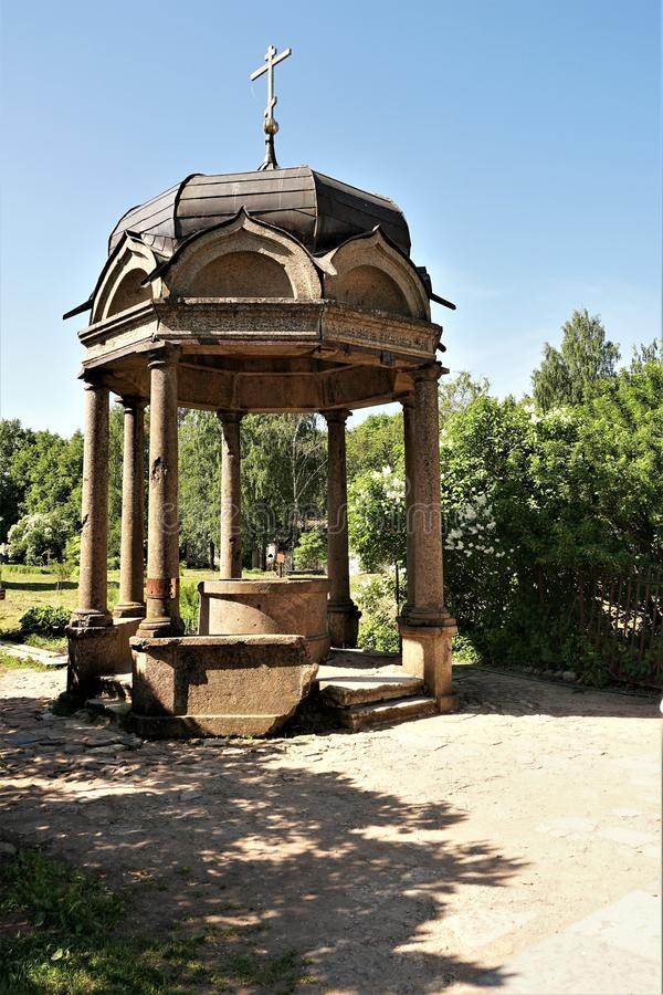 Novgorod may 2018 parched holy spring in the friary. Granite historical building, park, sunny day, old charms, green plants royalty free stock photo