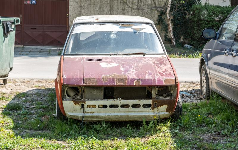 Old damaged and rusted Yugoslavian Zastava Yugo car with broken windscreen or windshield and peeled paint on the hood. stock photo