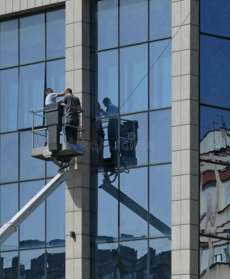Two workers on the crane with  hydraulic aerial platform fixing problem on glass building royalty free stock photography